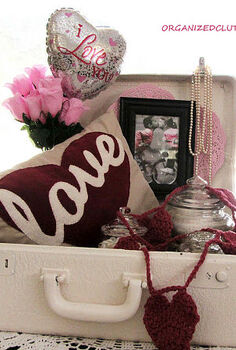 a valentine s day love suitcase, repurposing upcycling, seasonal holiday d cor, valentines day ideas, Jars of buttons and thread the pillow a crocheted heart garland a framed card Dollar Tree balloon roses paper heart doily and pearls complete my suitcase vignette