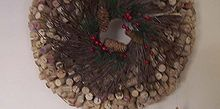 diy cork wreath, crafts, seasonal holiday decor, wreaths, My 1 000 wine cork wreath made from corks wreath form Dollar store twig wreath in front two hand crafted wooden ornaments I had