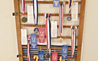 an old crib railing becomes a great place to display ribbons and hide an ugly wall, repurposing upcycling, wall decor, Cover an ugly wall vent get creative by using an old crib railing to display award ribbons