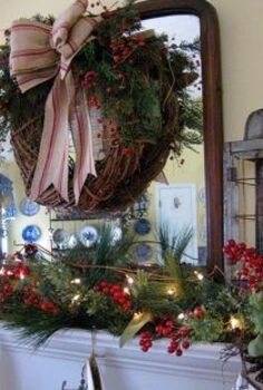 my farmhouse christmas mantel, christmas decorations, seasonal holiday decor, wreaths, Lots of greenery with red berries rustic lanterns and a grapevine wreath with a grain sack ribbon make up my farmhouse mantel