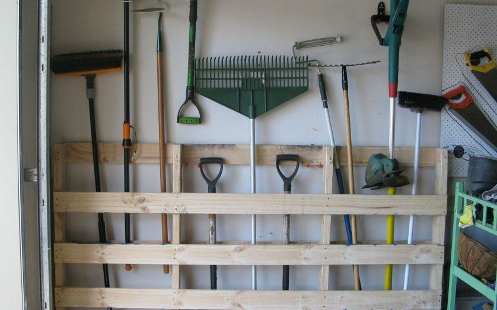 s 17 little known ways to use your wasted wall space, organizing, storage ideas, wall decor, Attach pallets to the garage wall for tools