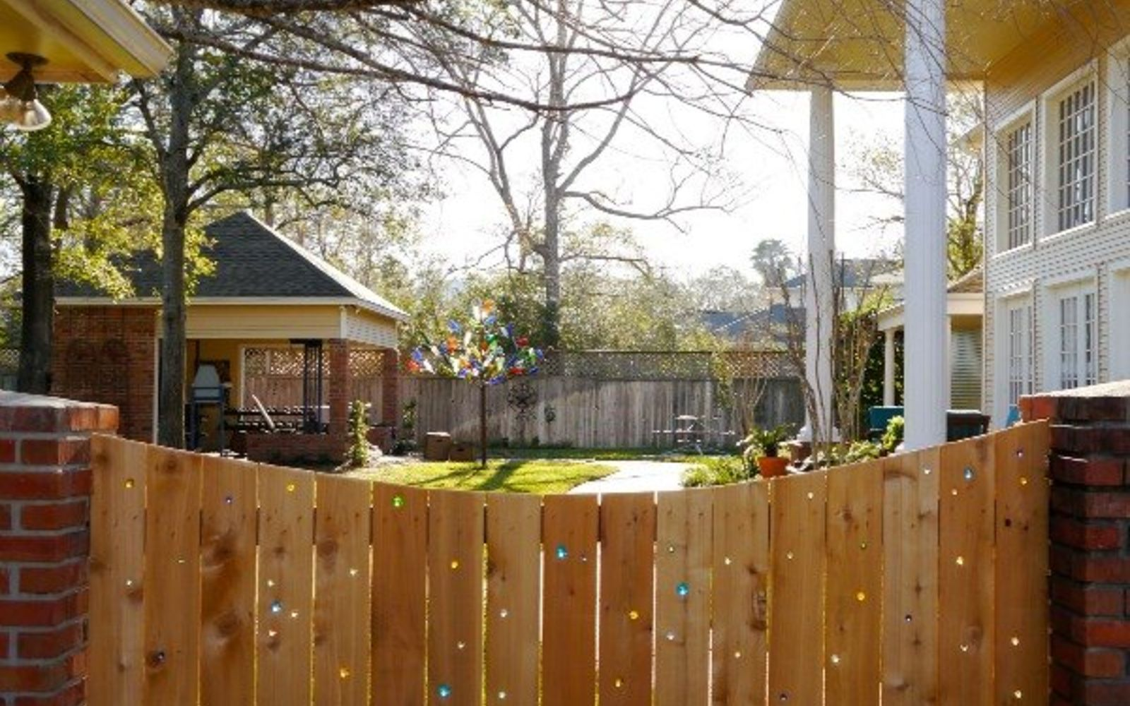 s 15 privacy fences that will turn your yard into a secluded oasis, curb appeal, fences, Drill holes in a plain fence to add marbles
