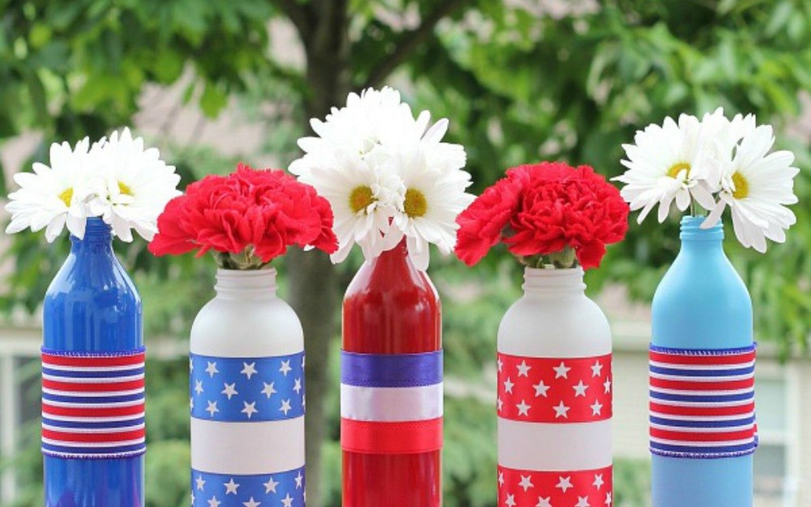 s 13 july 4th decorations that will blow your bbq guests away, crafts, outdoor living, seasonal holiday decor, Upcycle bottles into bursting flower displays