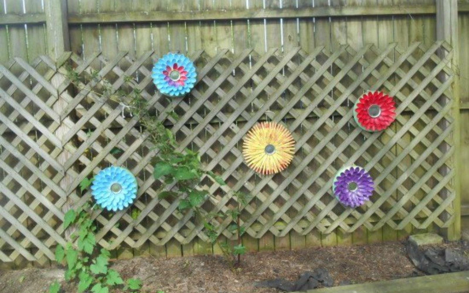 s 11 brilliant ways to reuse plastic spoons, Paint them into colorful fence flowers