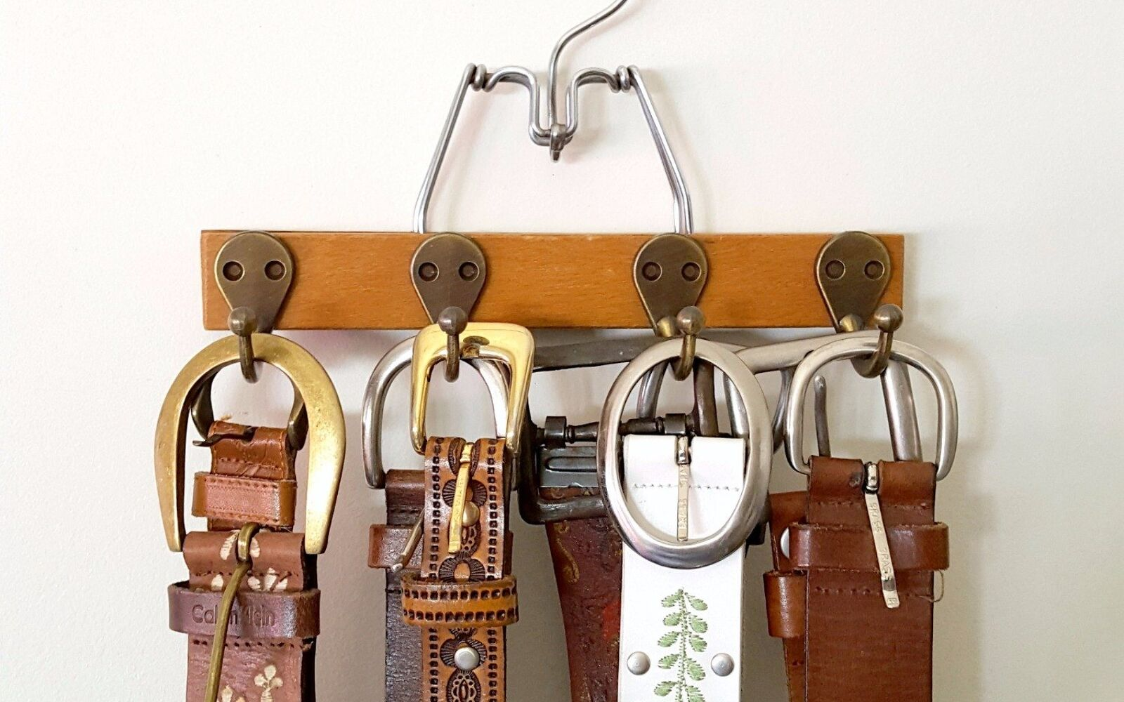 s 30 fun ways to keep your home organized, Get Your Belts In Order With A Mini Hanger