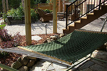 outdoor bonus room take full advantage of all the space in your yard and, decks, gardening, landscape, outdoor living, patio, The small boulder wall creates a grade change along with the chilton flagging for the patio create a more relaxed and informal feel to this room under the deck The sweet hammock goes along way in making this an awesome oasis