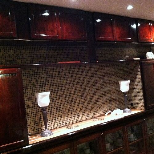 Unstained cabinets stained in red mahogany.
