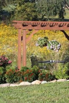 ornamental peppers in the landscape spice up your flower beds and your taste buds, flowers, gardening, landscape, outdoor living, The big bushy red poinsettia plants add color to the upper pergola area