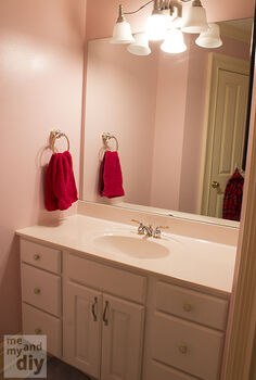 half bathroom reveal, bathroom ideas, home decor, This is the before pink walls white cabinets huge mirror on the wall