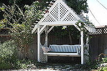 arbor swing, flowers, outdoor furniture, outdoor living, painted furniture, Arbor with a butterfly bush on left side and stephanotis flowers growing on both sides