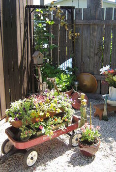 repurposed red wagons made into planters in front of a bed spring trellis fill a back, gardening, repurposing upcycling, Old forgotten wagons with a new life as adorable planters I least I think they re lovely sit in front of a bedspring trellis The mirror behind the trellis is from a closet door