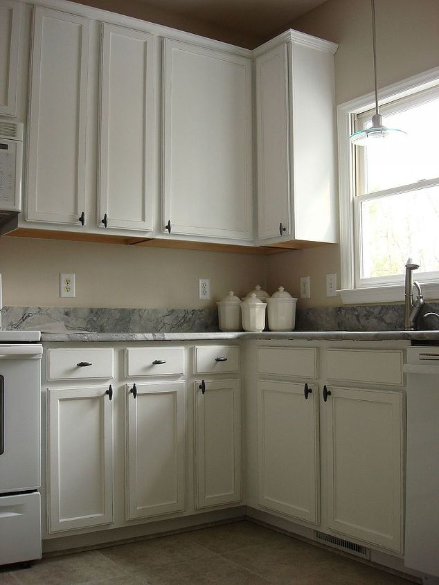 Old oak cabinets painted white and distressed hometalk for Making old kitchen cabinets look modern