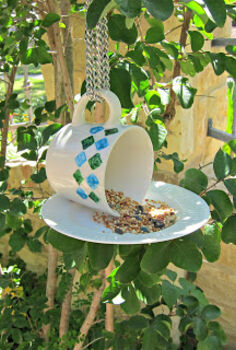 whimsical bird feeder, gardening, outdoor living, repurposing upcycling, This is what it looks like with bird seed in it If it s windy where you live you could glue this to a post to make it more stable