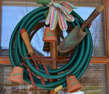 a garden hose wreath, home decor, wreaths, A garden hose small terracotta pots and gloves for a bow