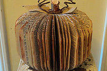 transform an old paperback book into a decorative pumpkin, crafts, The finished project with a birch stem burlap leaves bark covered wire and painted paper edges