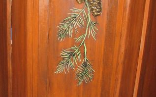 rustic kitchen cabinets get a country design with plaster stencils, home decor, kitchen cabinets, kitchen design, The pine cones were cast from a mold primed and painted then attached over the pine branch design A coat of varnish protects the design