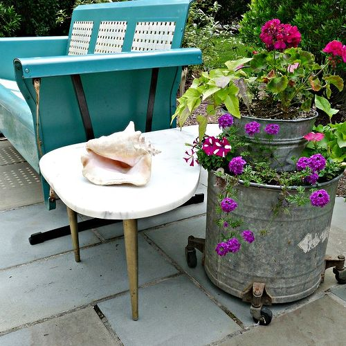 Vintage porch glider, mid-century marble table, old mop buckets.  Click link for more pics:http://eclecticallyvintage.com/2012/06/my-patio-reveal/