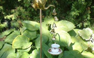 vintage coffee pot wind chimes, gardening, repurposing upcycling, Vintage Coffee Pot Wind Chimes Small Christmas Bells are tied to fishing line and are poured from the coffee pot spout into a lovely cup and saucer held up by a green bottle covered stake