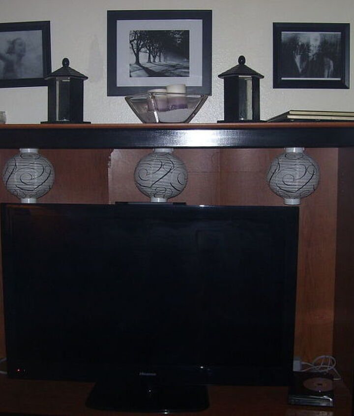My $45 entertainment center..I hung paper Chinese lanterns behind the tv (they light up)placed my candle holders ( I made out of bird feeders) on top and added another picture grouping.