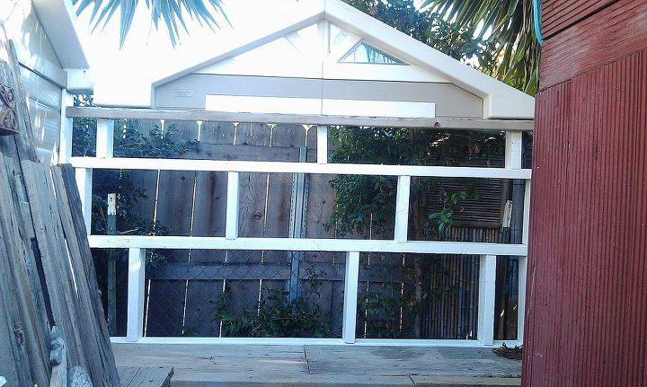"I built a wall of shelves out of discarded 2x4 pieces I found in a wood pile.  The  plastic  ""window"" on top is a replacement window to my aviary which this table butts up next to on the left. It ties the areas together."