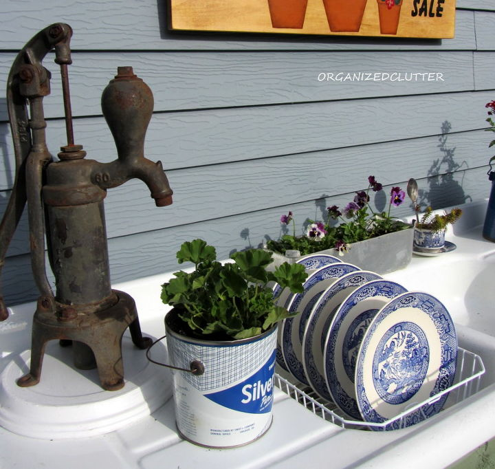 An old pump, a vintage lard pail, Blue Willow air drying in the sink, and a vintage aluminum angel food pan fill the left side of the potting bench.
