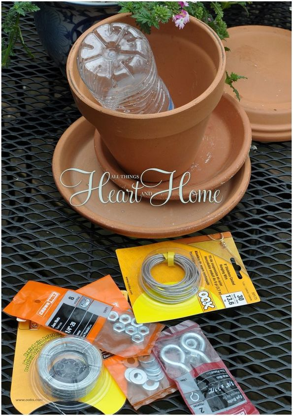 """Gather these easy to find supplies: Terra Cotta Pot, Saucers, Picture Hanging Wire, 5"""" Eye Bolt,2 Nuts, Fishing Swivel, Branch  & a water bottle! Soak your terra cotta in water over night to make drilling the holes easier..."""