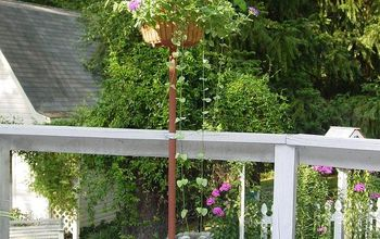 Old wire egg basket and thrift store floor lamp stand repurposed into an outdoor planter