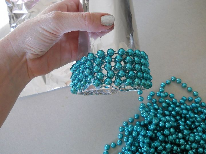 Using a bead of hot glue, stick your garland around your foil covered cone, starting at the bottom.