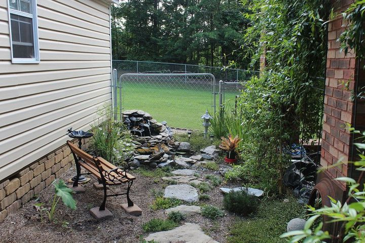 This is an after picture of the same area with small water garden and foot path. I found the tiny child's bench at an antique store in pieces. I planted Carolina Jasmine on trellises between the pillars of the carport.
