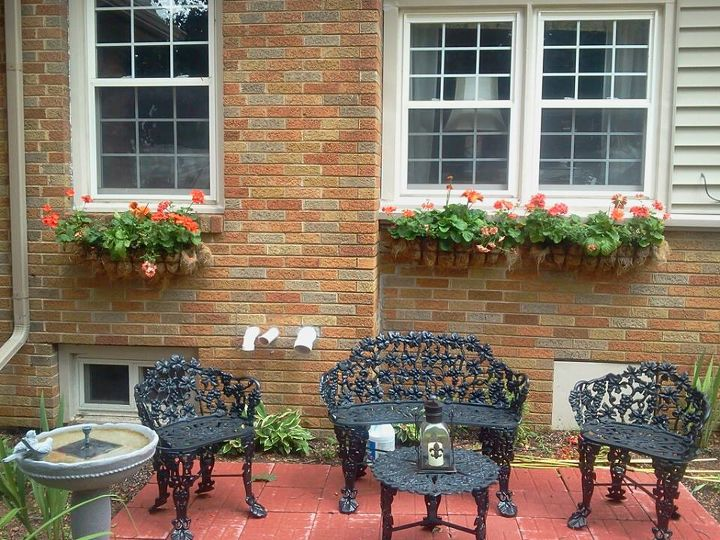 I added iron window flower boxes and planted gerbera daisies, geraniums, and verbena.