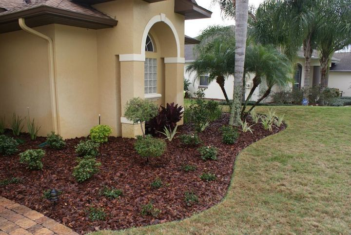 AFTER photo now shows a friendlier look. Notice that the maroon Hawaiian Tys are planted closer to the overhang for winter protection.