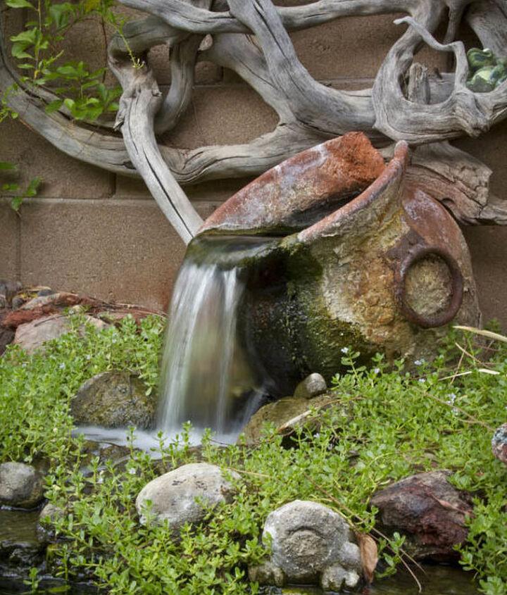 A rustic urn flows beneath dramatic driftwood art.