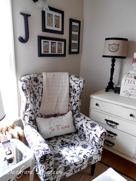 The pictures behind the chair are actually framed vintage needle packs or sewing cards.