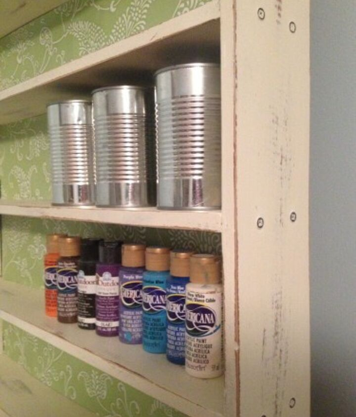 The shelf was painted and distressed and waxed. I lined it with contact paper from Target that cost only $5.00 for a big roll! Cheaper than scrapbook paper or wallpaper. And I upcycle old tin cans to hold suppies.