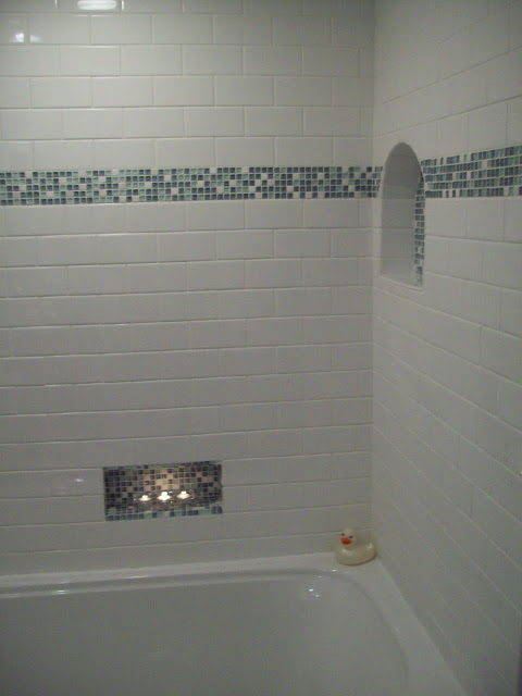 I used white subway tile with a small band of glass mosaic tile and two niches.  The lower niche was placed off center and low so it can be reached when taking a bath and it works wonderfully!