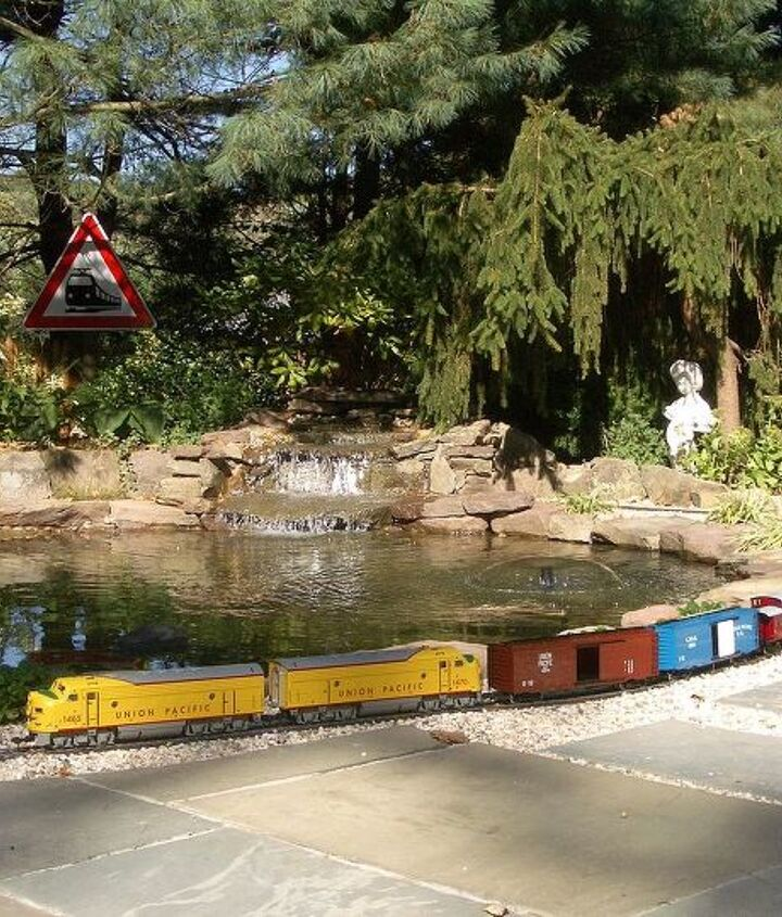 Outdoor train thru the waterfall and coming around the pond