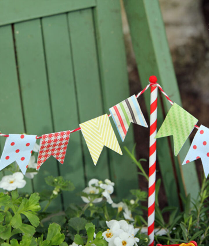 Flag bunting made out of scrapbooking paper, bakers twine and tiny red pom poms.  The poles are straw covered shish kebab skewers
