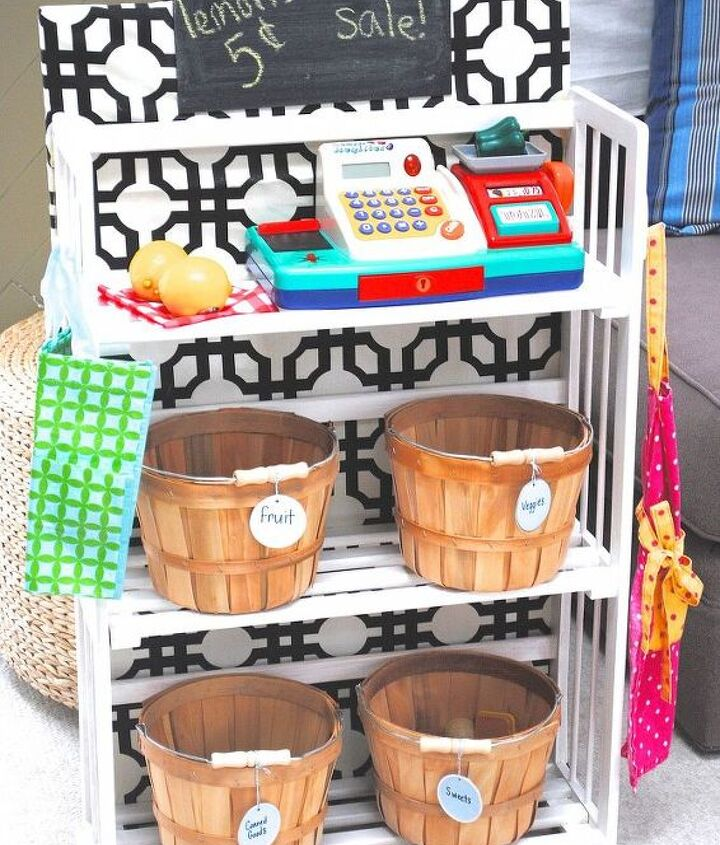 A sweet little pretend play grocery store with bushel baskets of food, a cash register, grocery bag, and grocer's apron.