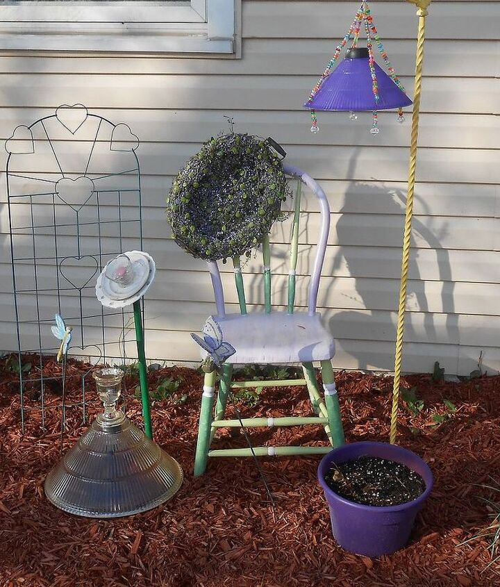 Recycled chair and lite post with a purple plastic lamp shade into solar and a heavy glass shade (on the ground with a solar lite inside, along with a recycled glass blossom.