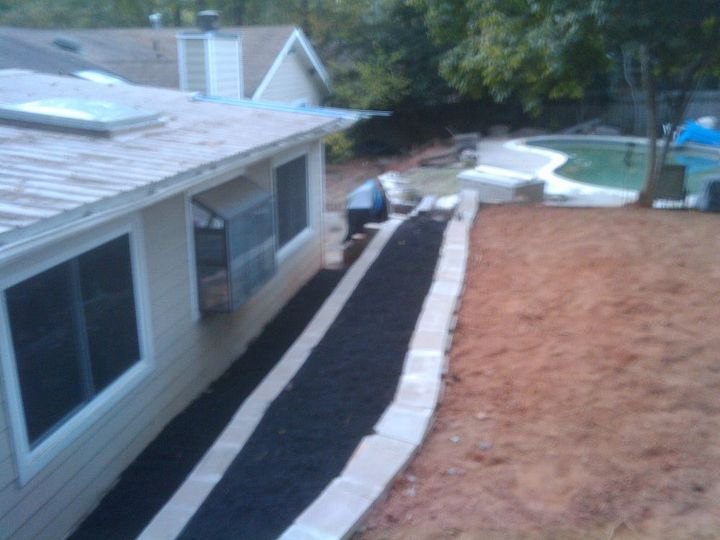 The extra dirt directs water from the neighbors around the house and downhill.