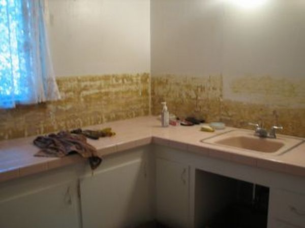 more pink tiles removed from the wall behind the counter top.