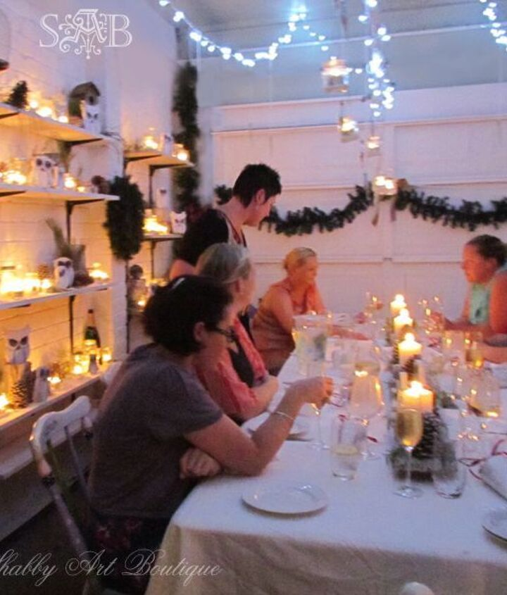 A 3 metre long branch hanging from the ceiling supports hanging candles and fairy lights.