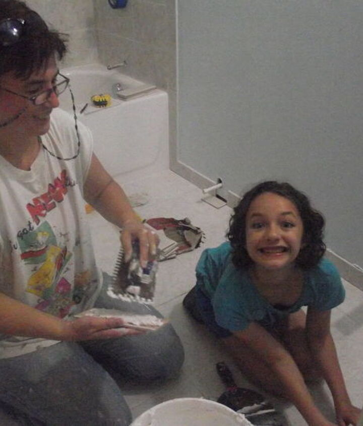 Here I am, teaching my granddaughter how to lay the bullnose {baseboard tiles}.