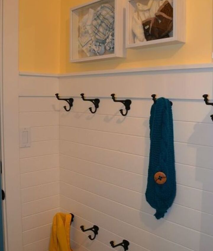 white horizontal paneling, two rows of hooks and custom shadow box art with baby clothes at thehappyhousie