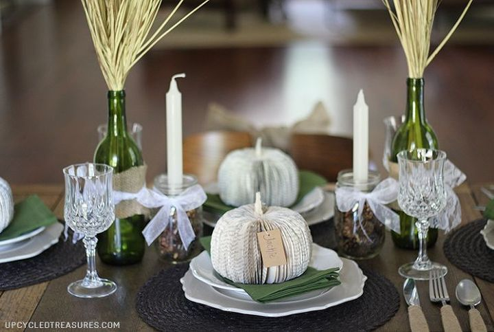 Wine bottles with burlap and lace details. Filled with wheat accents. Mason jars filled with baby pine cones and a tapered candle