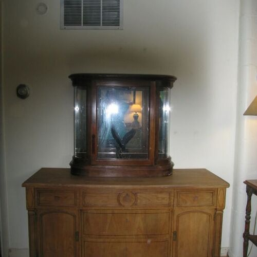 This is one of the two walls without anything on them.  The grate above is the intake for the furnace.  The cabinet is the buffet with a little curio cabinet on top.  The cabinet has curved glass and a mirrored back  & 1 schel inside.
