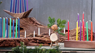 , A reindeer made from Christmas tree trunks and branches stands alongside a menorah made from Christmas tree trunks