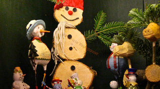 , A large snowman made from Christmas tree trunks and branches stands alongside other snow people and a reindeer made from Christmas tree trunks