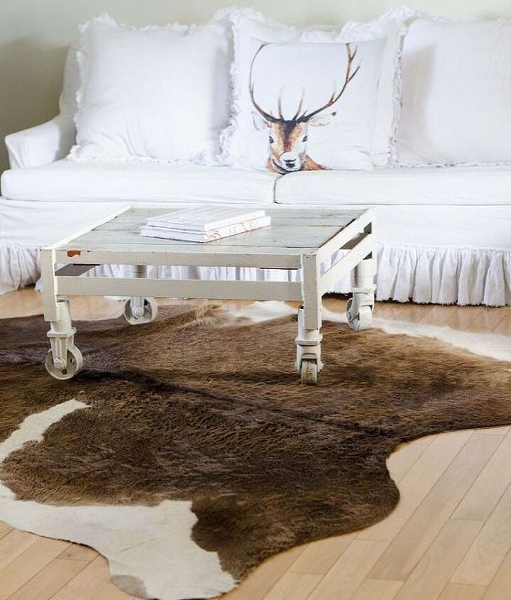 chandeliers and cow hide rugs in white living room decor, home decor, lighting, living room ideas, repurposing upcycling, reupholster