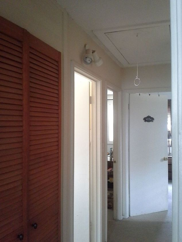 Angling to the left wall from  hallway entrance, is a louvered closet for linens. Directly across from the bathroom door.